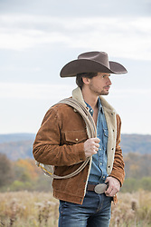 hot cowboy with a lasso on a mountain range