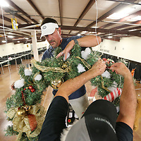 Sean Koehn begins to hang wreaths at the Tupelo Furniture Market building V as volunteers get ready for next weeka annual Celebration Village.