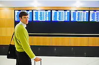 A early 30's Caucasian male business traveler in an airport looking tired and frustrated after looking at the arrivals / departures monitors.20050916_MR_D.20050916_PR_A