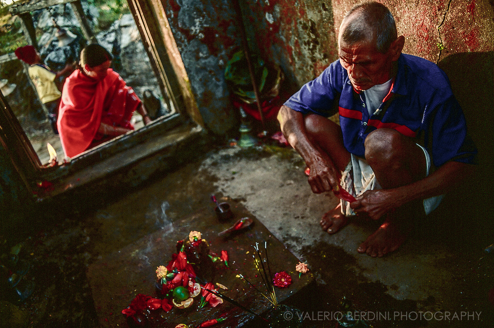 A hindu man prepares some floral offering in a temple in Bandipur