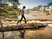 "01 MARCH 2014 - MAE SOT, TAK, THAILAND: A Burmese boy crosses a temporary footbridge to a boat landing in the Moie River in Mae Sot. Boats from Myawaddy, Myanmar (the buildings in the background are in Myawaddy) drop and pick up passengers for the short trip across the river. Mae Sot, on the Thai-Myanmar (Burma) border, has a very large population of Burmese migrants. Some are refugees who left Myanmar to escape civil unrest and political persecution, others are ""economic refugees"" who came to Thailand looking for work and better opportunities.    PHOTO BY JACK KURTZ"