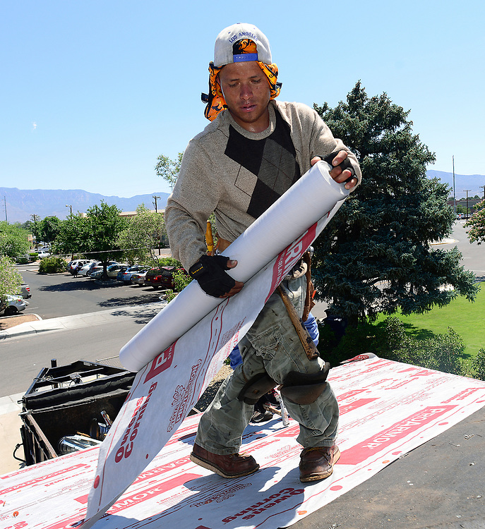 apl062117b/ASECTION /pierre-louis/JOURNAL 062117<br /> Otero and Sons Roofer  Norlan Coello,,works on a Hoffmantown home's shingle roof  in Wednesday's sweltering temperatures  .Photographed  on Wednesday June  21,  2017. .Adolphe Pierre-Louis/JOURNAL