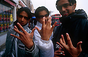 "Three young British Asians pose in the street to show their gangland signs in Southall, west London. ""Throwing up"" a gang sign (e.g., ""Stacking,"" ""walk"") with the hands is one of the most known and obvious forms of ""claiming."" It is used in many situations where other identifiers may not be possible or appropriate, and it can also show that a gang member is in the area to ""do business"" as opposed to just passing through. Usually these signs are made by formation of the fingers on one or both hands to make some sort of symbol or letter."