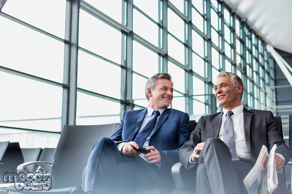 Mature businessmen talking while sitting and waiting for boarding in airport