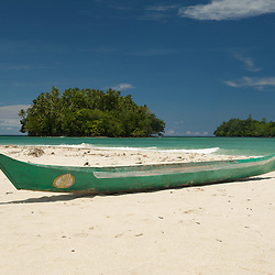 Logboat on a white sandy beach ready for fishing.