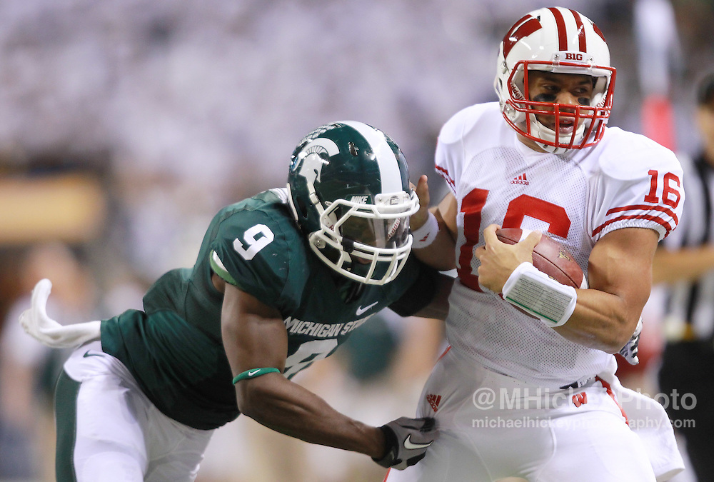 Dec. 03, 2011; Indianapolis, IN, USA; Wisconsin Badgers quarterback Russell Wilson (16) is tackled by Michigan State Spartans safety Isaiah Lewis (9) at Lucas Oil Stadium. Mandatory credit: Michael Hickey-US PRESSWIRE