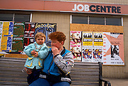 A young mother holds her child while sitting on a street bench outside a closed 1990s Job Centre. As a result of the 1987 a stock market collapse, the UK economy experienced a downturn resulting in public services suffering a reduction, including the closure of the Job Centres of the day. The recession of the early 1990s describes the period of economic downturn affecting much of the world in the late 1980s and early 1990s.