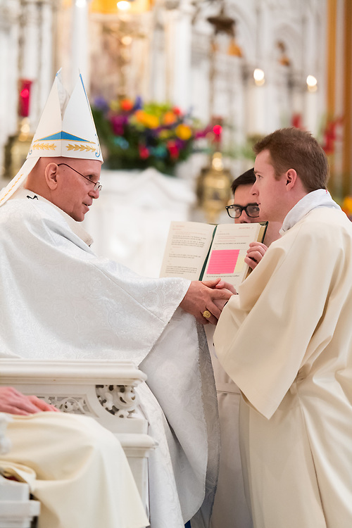 DENVER, CO - MAY 13: Denver Archbishop Samuel Aquila holds John Mrozek II's hands for the promise of respect and obedience for his ordination of the priesthood at the Cathedral Basilica of the Immaculate Conception on May 13, 2017, in Denver, Colorado. (Photo by Daniel Petty/for Denver Catholic)