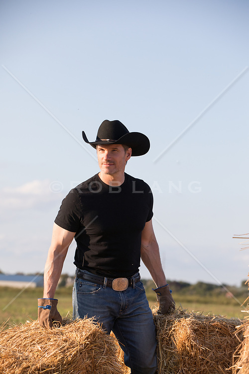 hot cowboy outdoors carrying bales of hay