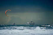 Stand up surfers paddle along the coast of Venice Beach, Calif.