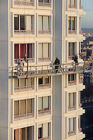 Looking out over painters adding a fresh coat of white paint to a tall apartment building in Paris, France.