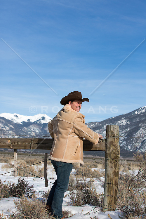 cowboy leaning on a fence in the Wintertime