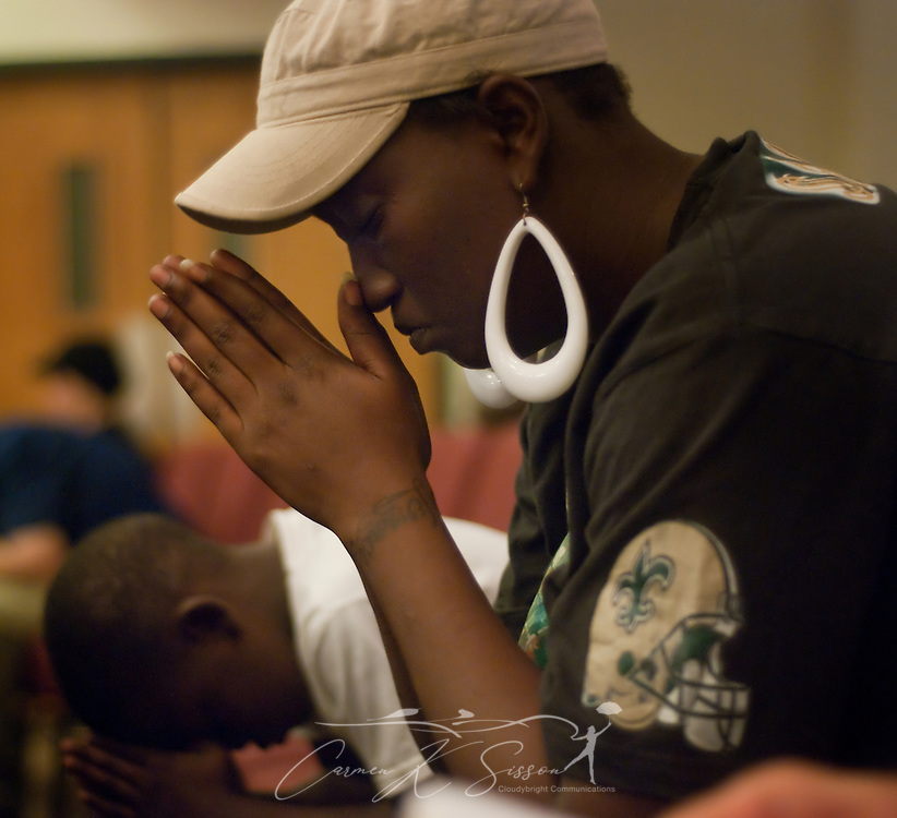 Shelita Woods-Muse and her son, Rashad Woods, bow their heads during a Community Crisis prayer service May 26, 2010 at First Baptist Church in Chalmette, La. Nearly 100 coastal residents attended the service to pray for protection, comfort, guidance, and mercy as BP continues to battle the oil spill in the Gulf of Mexico. (Photo by Carmen K. Sisson/Cloudybright)
