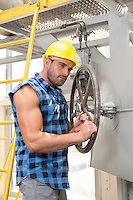 Young worker fixing industrial valve with wrench