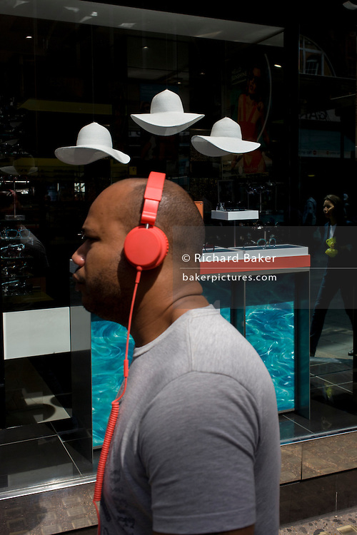 Man listening to mp3 music walks past a sunglasses shop featuring three hats suspended from the store window ceiling.