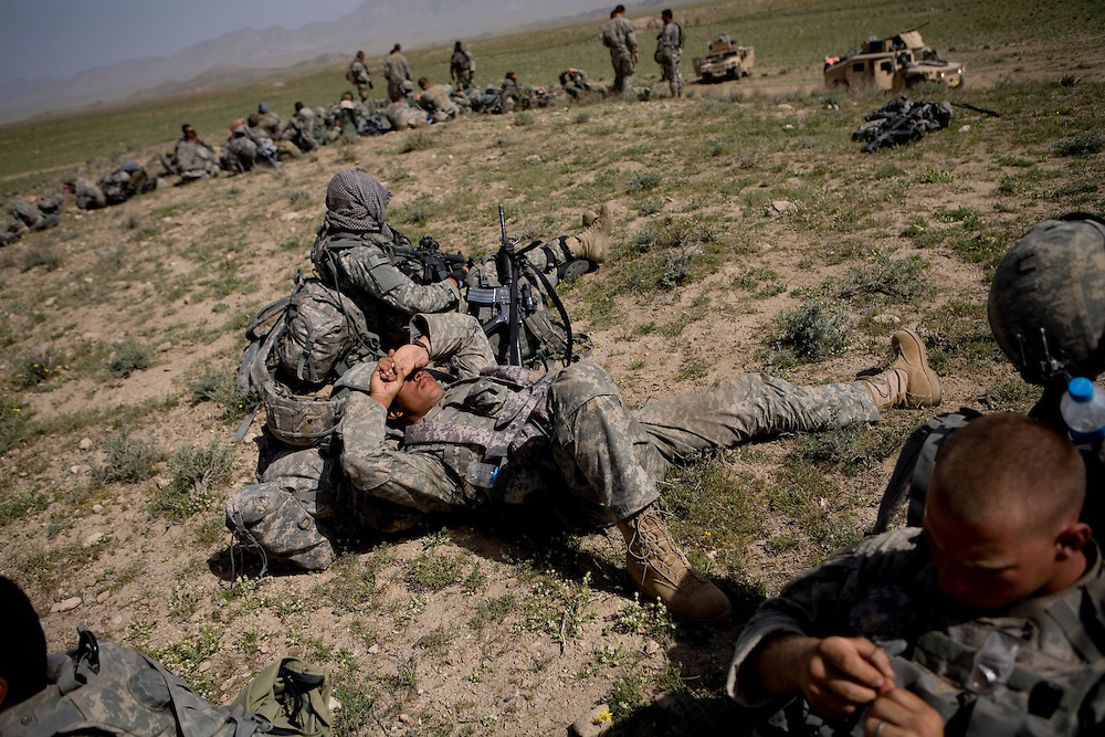 Members of the 82nd Airborne's 1/508 Alpha Company wait for hours in the baking sun for an overdue helicopter ride back to Forward Operation Base Diablo after a mission in remote Kandahar province, Afghanistan on Wednesday, March 28, 2007.