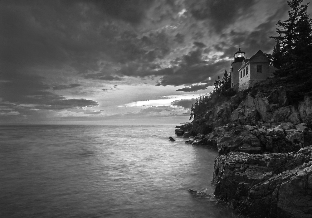 Black and White New England photography of the iconic Bass Harbor Head Light located on Mount Desert Island within Maine Acadia National Park on the southeast corner of MDI. The lighthouse towers over the swirling Atlantic Ocean and seacoast, marking the entrance to Bass Harbor and Blue Hill Bay. It is one of the most iconic scenery of Acadia NP as Bass Harbor Light is dramatically located on the edge of rugged cliffs.<br /> <br /> This New England B&W lighthouse fine art photography image is available as museum quality photography prints, canvas prints, acrylic prints or metal prints. Fine art prints may be framed and matted to the individual liking and decorating needs:<br /> <br /> https://juergen-roth.pixels.com/featured/maine-bass-harbor-head-light-juergen-roth.html<br /> <br /> Good light and happy photo making!<br /> <br /> My best,<br /> <br /> Juergen<br /> Prints: http://www.rothgalleries.com<br /> Photo Blog: http://whereintheworldisjuergen.blogspot.com<br /> Instagram: https://www.instagram.com/rothgalleries<br /> Twitter: https://twitter.com/naturefineart<br /> Facebook: https://www.facebook.com/naturefineart