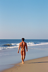 naked bodybuilder walking alone the shore of the beach
