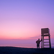 Silhouette of a man standing by a lifeguard stand at sunrise. Old Orchard Beach, Maine