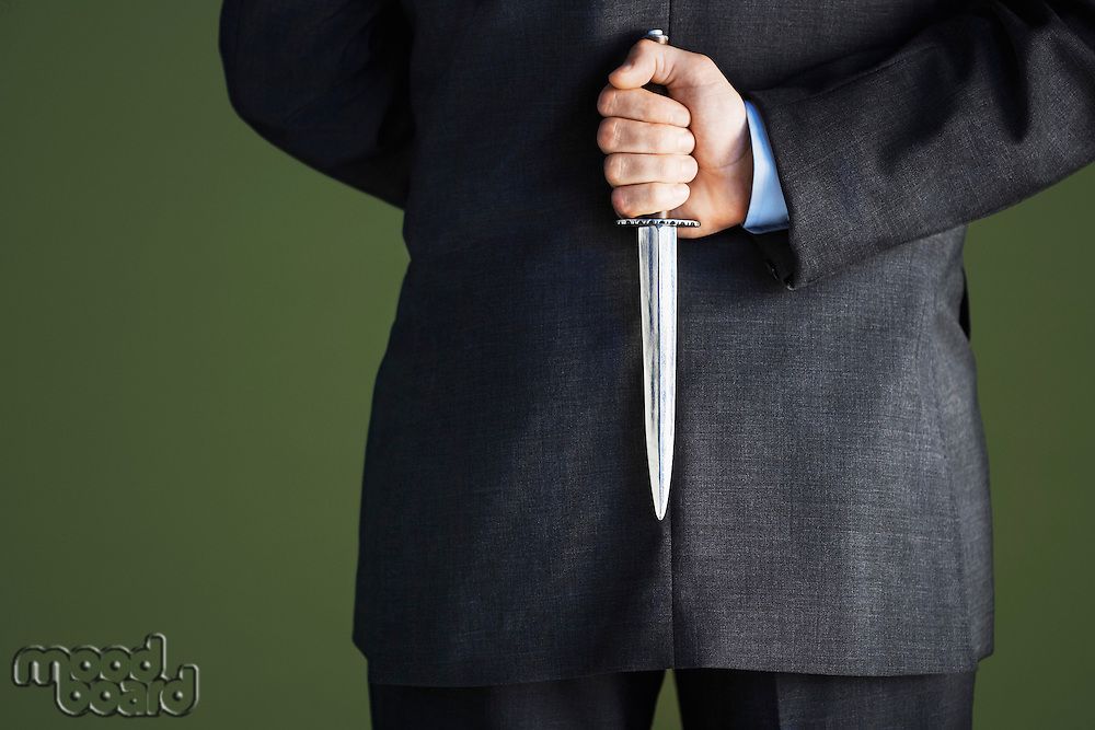 Mid-adult businessman standing holding knife behind back mid section back view