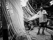 "29 DECEMBER 2018 - BANGKOK, THAILAND: A woman stretches longevity noodles during the drying process in front of her family shophouse. The family has been making traditional ""mee sua"" noodles, also called ""longevity noodles"" for three generations in their home in central Bangkok. They use a recipe brought to Thailand from China. Longevity noodles are thought to contribute to a long and healthy life and  are served on special occasions, especially Chinese New Year, which is February 4, 2019. These noodles were being made for Chinese New Year.     PHOTO BY JACK KURTZ"