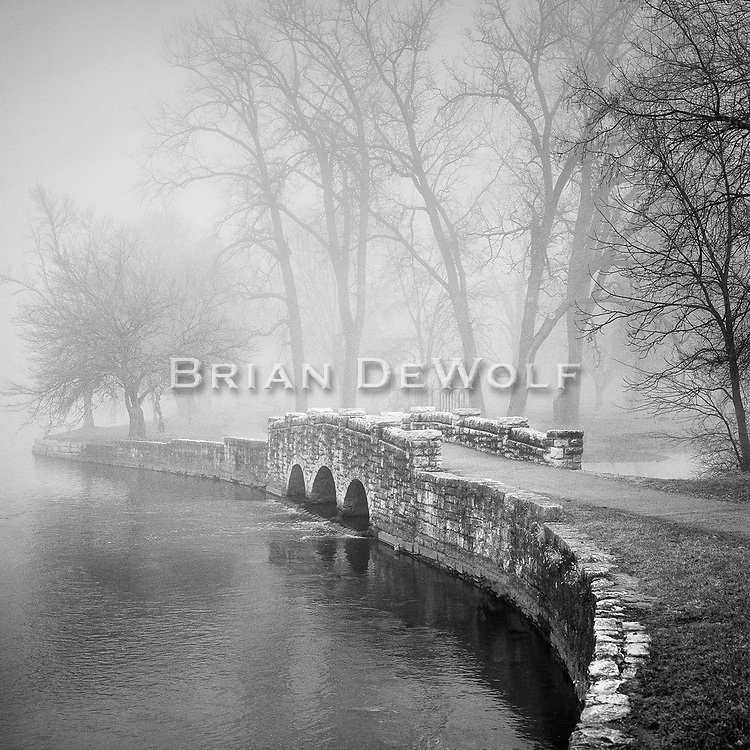 This is an open edition print. Canvas prints have a 2 inch black border so it can be gallery wrapped. The print is made using pigmented inks on museum-grade canvas or watercolor paper. Each print also gets a light coating of lacquer protective spray. Each print is hand signed by Brian DeWolf.  The little stone bridge at Island Park in Geneva, Illinois seems like it came from a fantacy when surrounded by fog. It was built during the Great Depression when workers were greatful to be sweating out a day's pay.