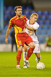 PODGORICA, MONTENEGRO - Wednesday, August 12, 2009: Wales' Jack Collison and Montenegro's Nikola Drincic during an international friendly match at the Gradski Stadion. (Photo by David Rawcliffe/Propaganda)