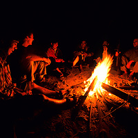 Tourists sit around a campfire, Ban Pak Ou, Luang Phrabang, Laos