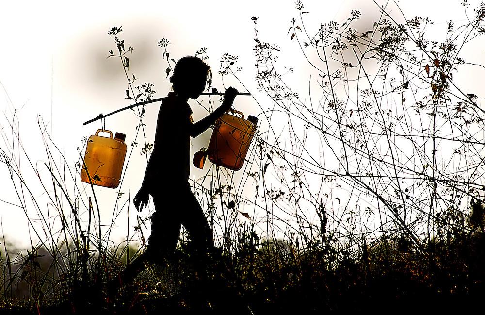 A girl taking home some water in Hongsa, Laos.