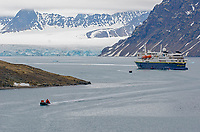 An anchored adventure ship and zodiacs coming ashore at Signehamna in Krossfjorden in front of Lilliehokbreen on the west coast of Spitsbergen in Svalbard archipelago, Norway.