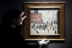 © Licensed to London News Pictures. 10/12/2012. London, UK. A Christie's employee adjusts 'At the Mill Gate' (1945) (est. GB£1,200,000-1,800,000) by Laurence Stephen Lowry at a press view for an evening auction held at King Street in London today (10/12/12). The evening auction, entitled 'Rule Britannia', and featuring over 185 lots by Britain's most influential modern artists, takes place on Wednesday the 13th Of December. Photo credit: Matt Cetti-Roberts/LNP