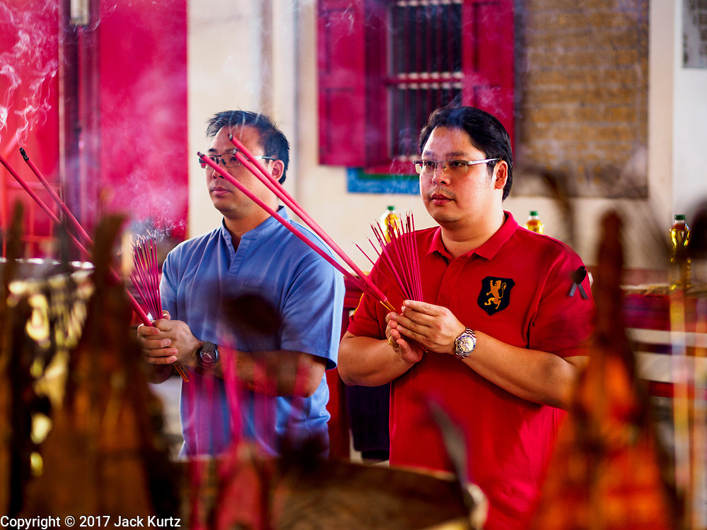 04 SEPTEMBER 2017 - BANGKOK, THAILAND: Men light prayer candles at Chaomae Thapthim Shrine before a food distribution event at the shrine. About 1,000 people came to the shrine for the annual food distribution. Staples, like rice and cooking oil, are donated to the shrine throughout the year and donated to poor people from the communities around the shrine. Food distributions like this are a tradition at Chinese shrines in Bangkok and a common way of making merit for the people who donate the staples.     PHOTO BY JACK KURTZ