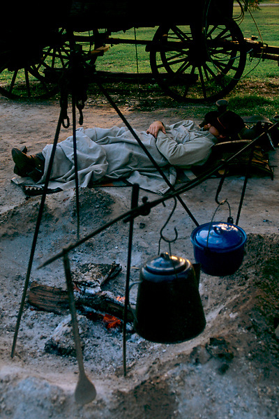 man sleeping beside a smoldering campfire