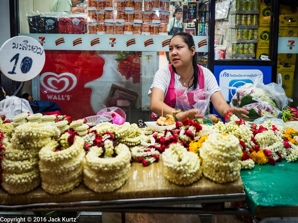 30 JUNE 2016 - BANGKOK, THAILAND: A flower garland on a sidewalk in front of a convenience store near Pak Khlong Talat. Sidewalk vendors around Pak Khlong Talat, Bangkok's famous flower market, face eviction if they reopen on July 1. As a part of the military government sponsored initiative to clean up Bangkok, city officials have been trying to shut down the sidewalk vendors around the flower market. The vendors were supposed to be gone by the end of March, but city officials relented at the last minute with a compromise allowing vendors to stay until June 30. When vendors dismantled their booths after business on June 30, they weren't sure if they will be allowed to reopen July 1. Some vendors have moved to new locations approved by the government but many have not because they can't afford the higher rents in the new locations.     PHOTO BY JACK KURTZ