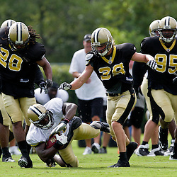 01 August 2009: New Orleans Saints running back Lynell Hamilton (30) is tripped up by defenders cornerback Usama Young (28) and safety Chris Reis (39) during New Orleans Saints training camp at the team's practice facility in Metairie, Louisiana.