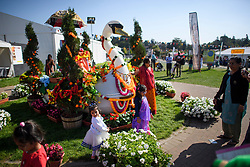 © Licensed to London News Pictures. 02/09/2018. Aldenham, UK. Children play next to a floral display at Bhaktivedanta Manor Temple in Aldenham, Hertfordshire during the Janmashtami Hindu festival. Janmashtami is an annual Hindu festival that celebrates the birth of Krishna. Bhaktivedanta Manor, the venue fo the event, was donated to the Hare Krishna movement in February 1973 by former Beatle George Harrison. Photo credit: Ben Cawthra/LNP