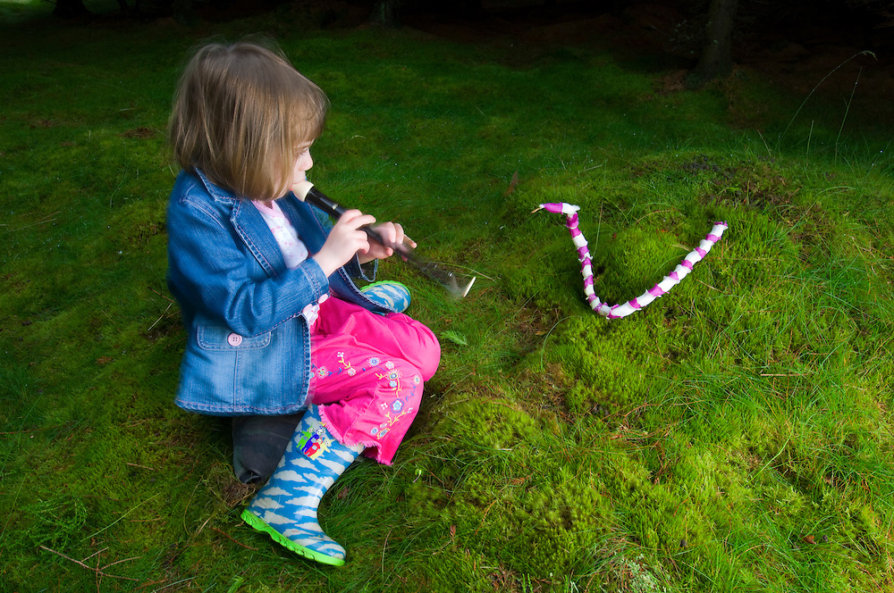 """Young girl """"charming"""" a foxglove snake"""