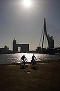 Twee fietsers rijden bij de Erasmusbrug in Rotterdam.<br /> <br /> Two cyclists near the Erasmusbridge in Rotterdam.