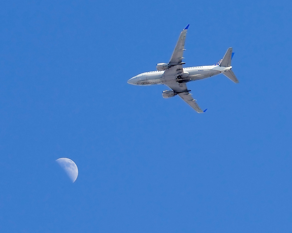 Photographed from my roof. A great place to wait for these shots. The planes are headed for LaGuardia Airport, and are a common site. Not so easy to get them though, in range of the moon.