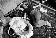 On the living room floor at home, a young mother grabs a few minutes to herself to exercises her pelvic floor muscles three weeks after giving birth to a baby girl who lies asleep in a Moses basket carry cot on the carpet. She rotates her hips to her right, twisting her body to regain strength in her lower torso, still sore from labour. This is from a documentary series of pictures about the first year of the photographer's first child Ella. Accompanied by personal reflections and references from various nursery rhymes, this work describes his wife Lynda's journey from expectant to actual motherhood and for Ella - from new-born to one year-old.