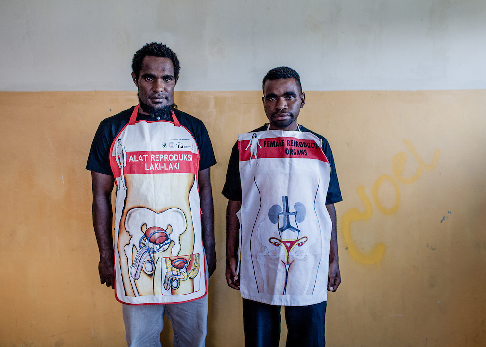 L-R: Roni (26) and Mecky (18), each wearing an apron with a diagram of the male and female reproduction organs, participate in a sexual reproduction and HIV/AIDS educational training conducted by the Public Health Development Foundation (YPKM), a Wamena based NGO.