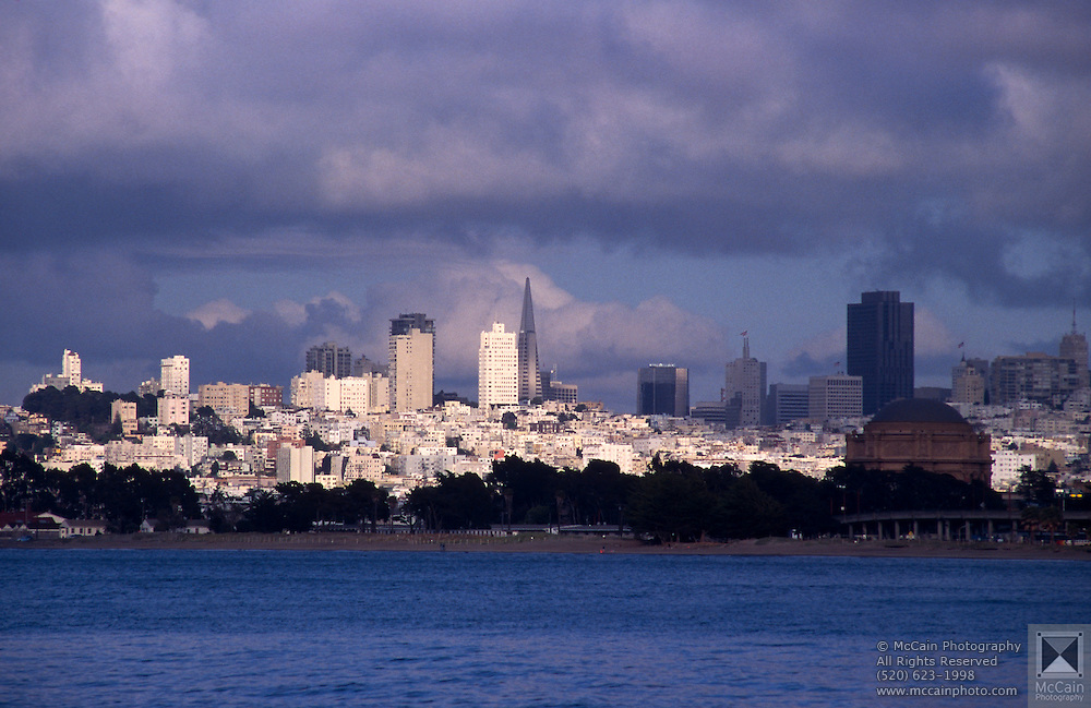View of city skyline from the bay with dark clouds overhead, San Francisco, California. The City and County of San Francisco is the fourth most populous city in California and the 14th most populous city in the United States, with a 2006 estimated population of 744,041. One of the most densely populated major cities in the U.S. San Francisco is part of the much larger San Francisco Bay Area, which is home to approximately 7.2 million people. The city is located on the tip of the San Francisco Peninsula, with the Pacific Ocean to the west, San Francisco Bay to the east, and the Golden Gate to the north...Subject photograph(s) are copyright Edward McCain. All rights are reserved except those specifically granted by Edward McCain in writing prior to publication...McCain Photography.211 S 4th Avenue.Tucson, AZ 85701-2103.(520) 623-1998.mobile: (520) 990-0999.fax: (520) 623-1190.http://www.mccainphoto.com.edward@mccainphoto.com.