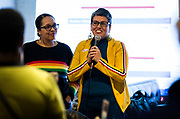 Ananda Mirilli, right, and Ali Muldrow speak to the crowd during the Madison School Board election watch party at Robinia Courtyard in Madison, Wisconsin, Tuesday, Feb. 19, 2019.