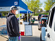 09 MAY 2020 - DES MOINES, IOWA: An artisan cheese maker talks to people in a drive through farmers' market in Des Moines. The Governor allowed farmers' markets across the state to reopen last weekend, but limited them to selling just food stuffs. They are not allowed to have entertainment or sell non-food items. Most farmers' markets in Iowa are taking a wait and see approach to reopening. The Downtown Farmers Market in Des Moines announced they won't reopen until July. Three vendors set up their own drive through farmers' market in the parking lot of Des Moines theatre Saturday. Hundreds of people got in line to buy fresh produce and artisan cheese. More than 11,670 people have tested positive for COVID-19 in Iowa and more than 250 have died from the disease.         PHOTO BY JACK KURTZ