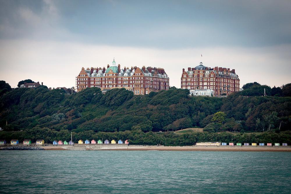 The iconic buildings of Metropole and The Grand buildings stand on The Leas at the top of Radnor Cliff tree lined hill, below is the Lower Leas Coastal Park and along the  Mermaid beach front are colourful Sandgate beach huts photographed from the sea in Folkestone, Kent, England, United Kingdom.  (photo by Andrew Aitchison / In pictures via Getty Images)