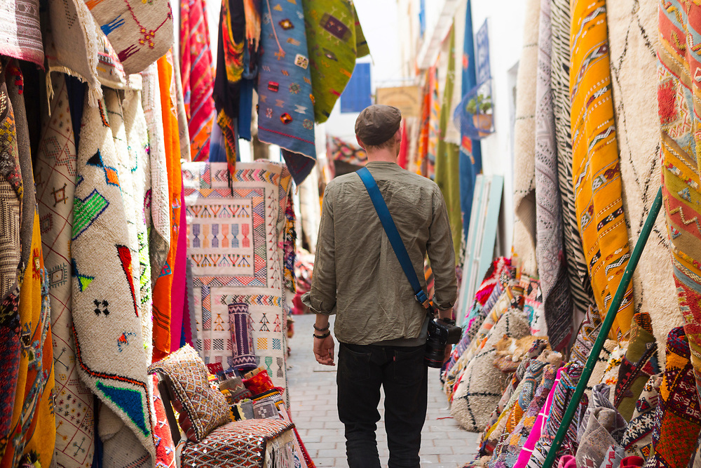 ESSAOUIRA, MOROCCO May 09th 2018 - Tourist shopping for artisanal arts and crafts in Essaouira Medina, Southern Morocco