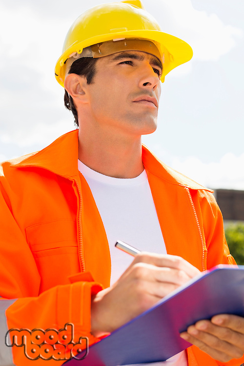 Male construction worker with clipboard looking away outside
