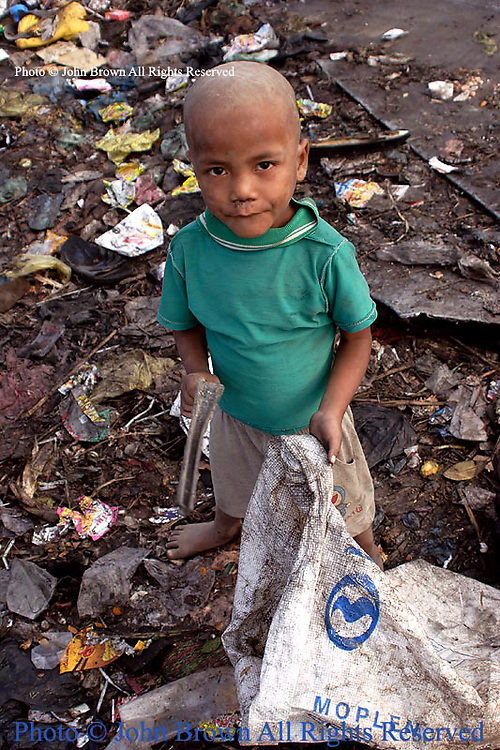 A young worker at The Stung Meanchey Landfill searches for recyclable material without footwear.
