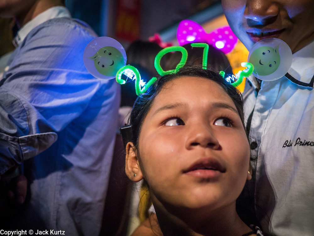 31 DECEMBER 2012 - BANGKOK, THAILAND: A girl wears a 2013 hat at the New Year's Eve party in Ratchaprasong Intersection in Bangkok. The traditional Thai New Year is based on the lunar calender and is celebrated in April, but the Gregorian New Year is celebrated throughout the Kingdom, especially in larger cities and tourist centers, like Bangkok, Chiang Mai and Phuket. The Bangkok Countdown 2013 event was called ?Happiness is all Around @ Ratchaprasong.? All of the streets leading to Ratchaprasong Intersection were closed and the malls in the area stayed open throughout the evening.    PHOTO BY JACK KURTZ
