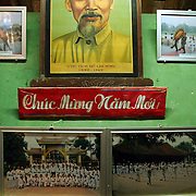 """A portrait of late revolutionary leader Ho Chi Minh sits above a sign reading, """"Happy New Year!"""" - celebrating the Vietnamese Lunar New Year."""